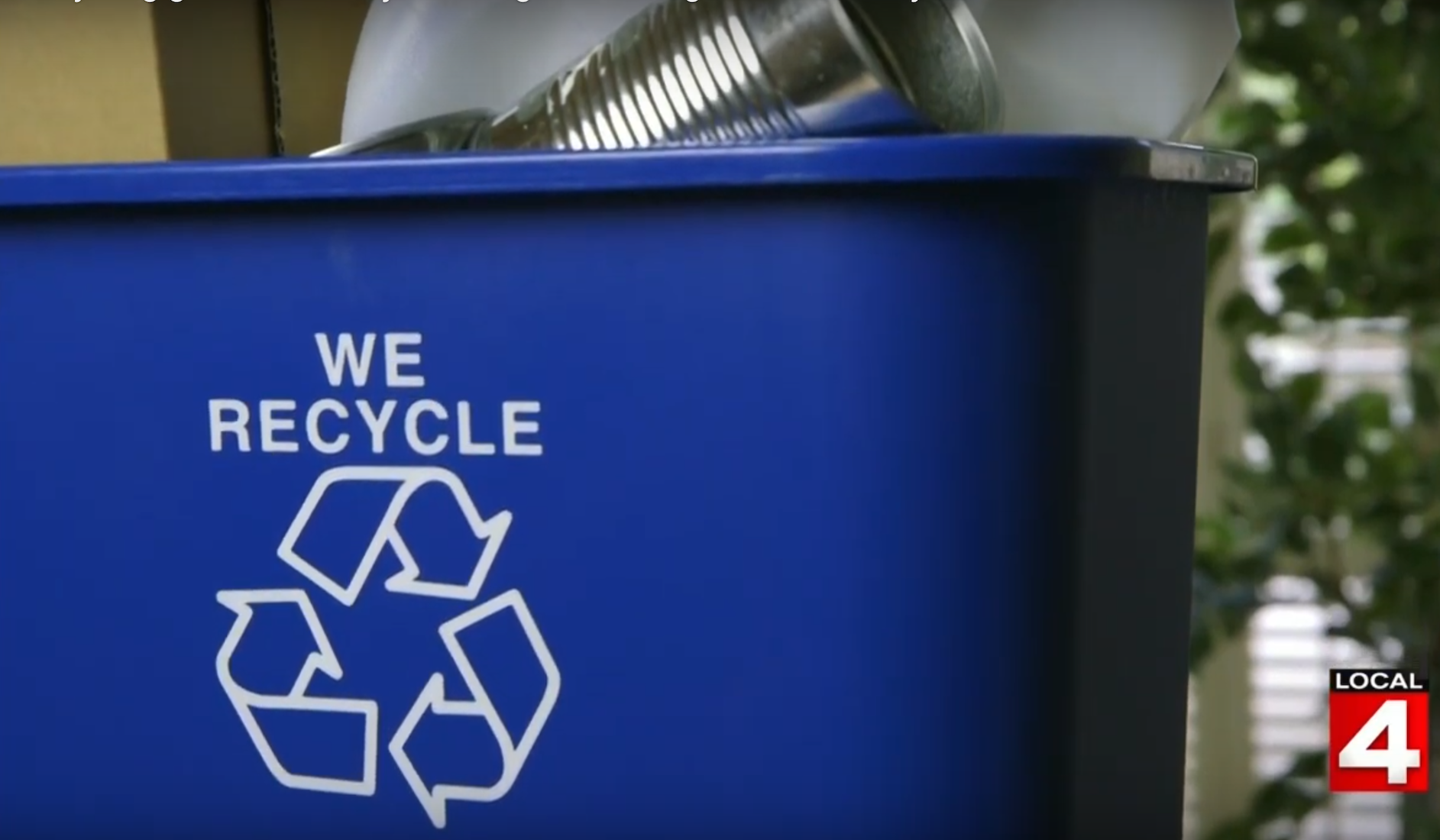 "Blue bin that says ""we recycle"" with recycleable products inside"