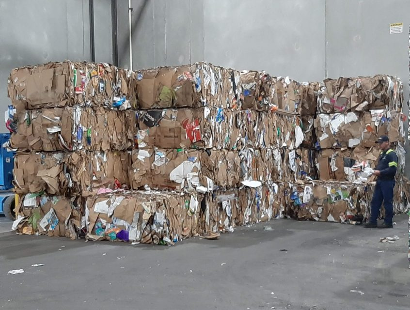 Flattened cardboard compressed into cubes, stacked and ready to be picked up for recycling