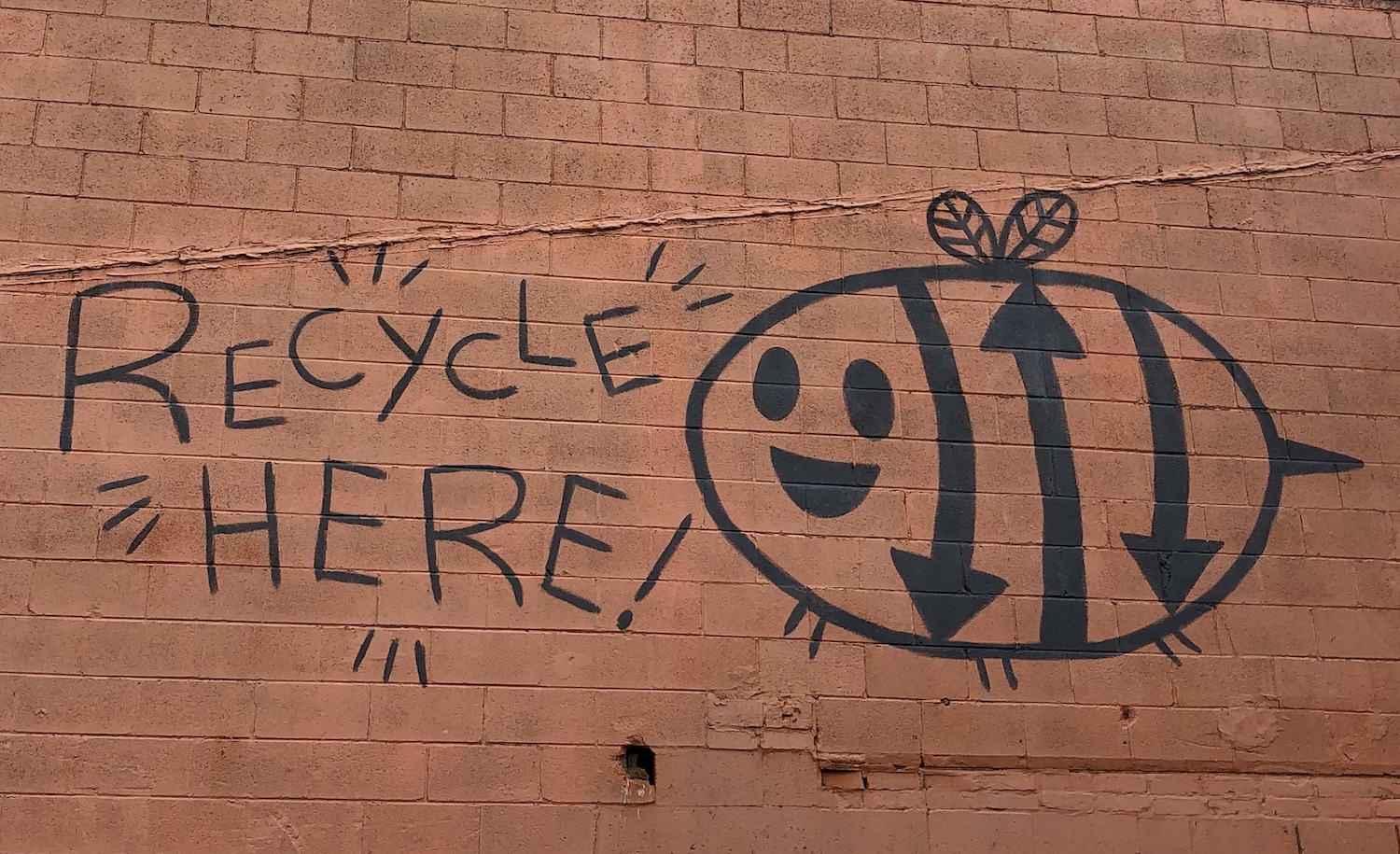 Recycle Here Logo painted on the side of a building
