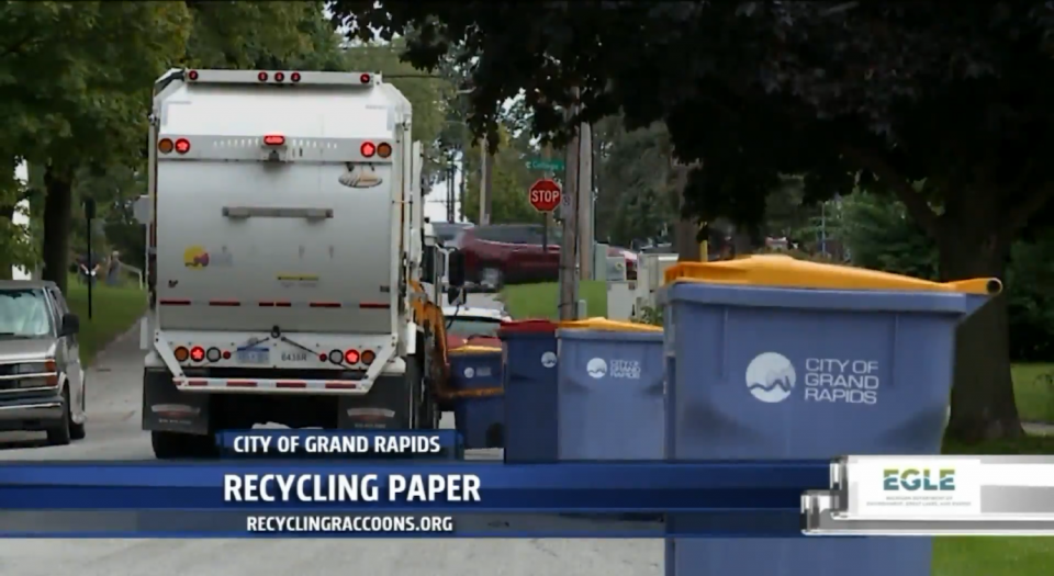 White recycling truck picks up blue curbside recycling bins in Grand Rapids