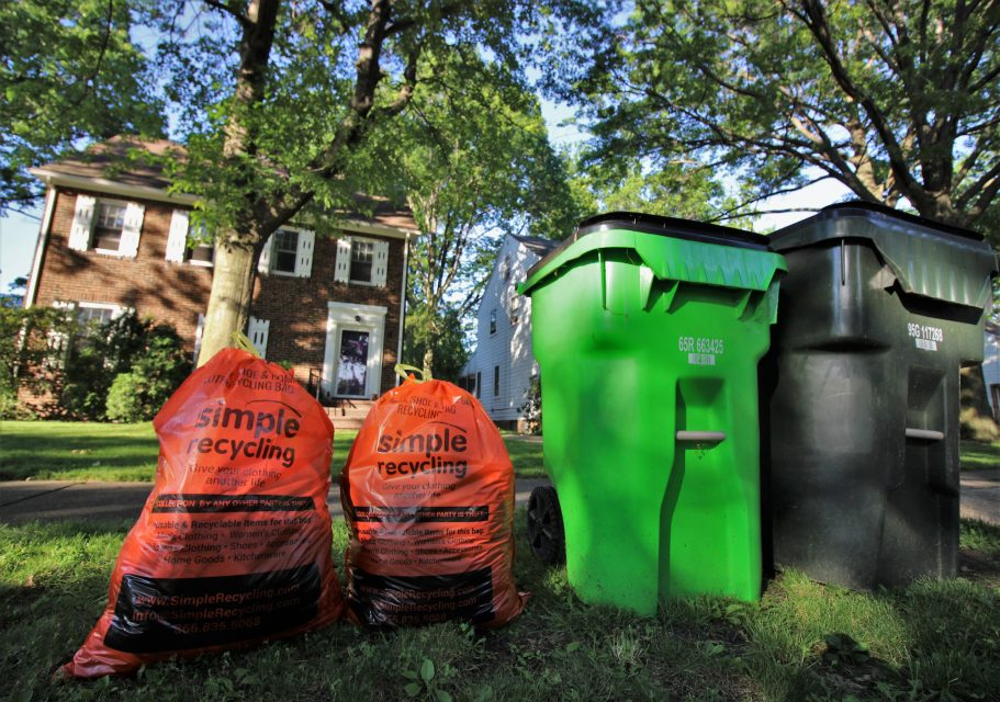 Two orange Simple Recycling bags to the left of a green recycling bin