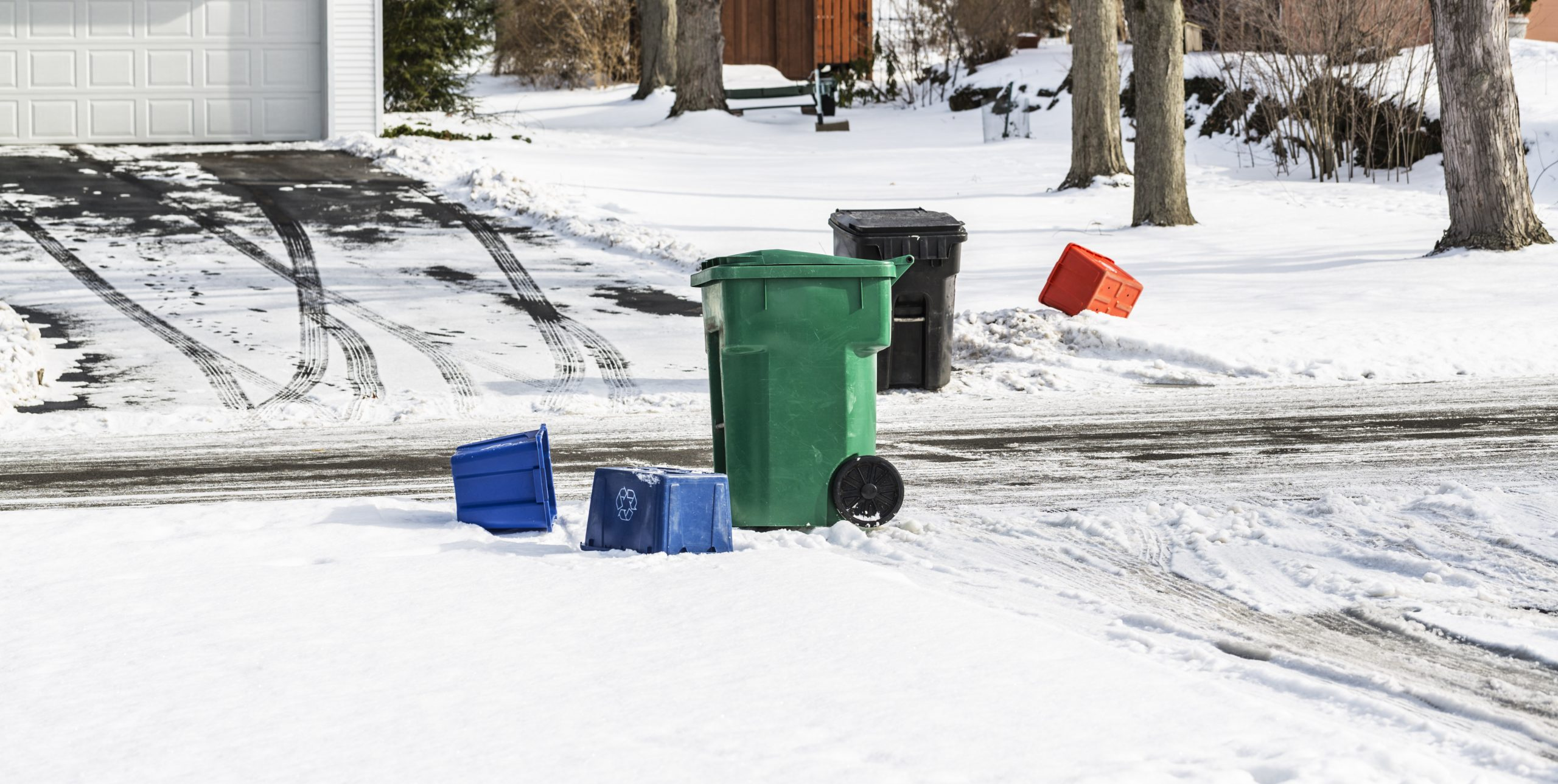 Empty wheeled garbage barrels and recycling containers are scattered/strewn near two opposite driveways along a suburban residential neighborhood street. Winter snow is on the ground and multiple slushy, messy tire tracks cris cross the driveways and the street. Must have been garbage/trash pickup day today.