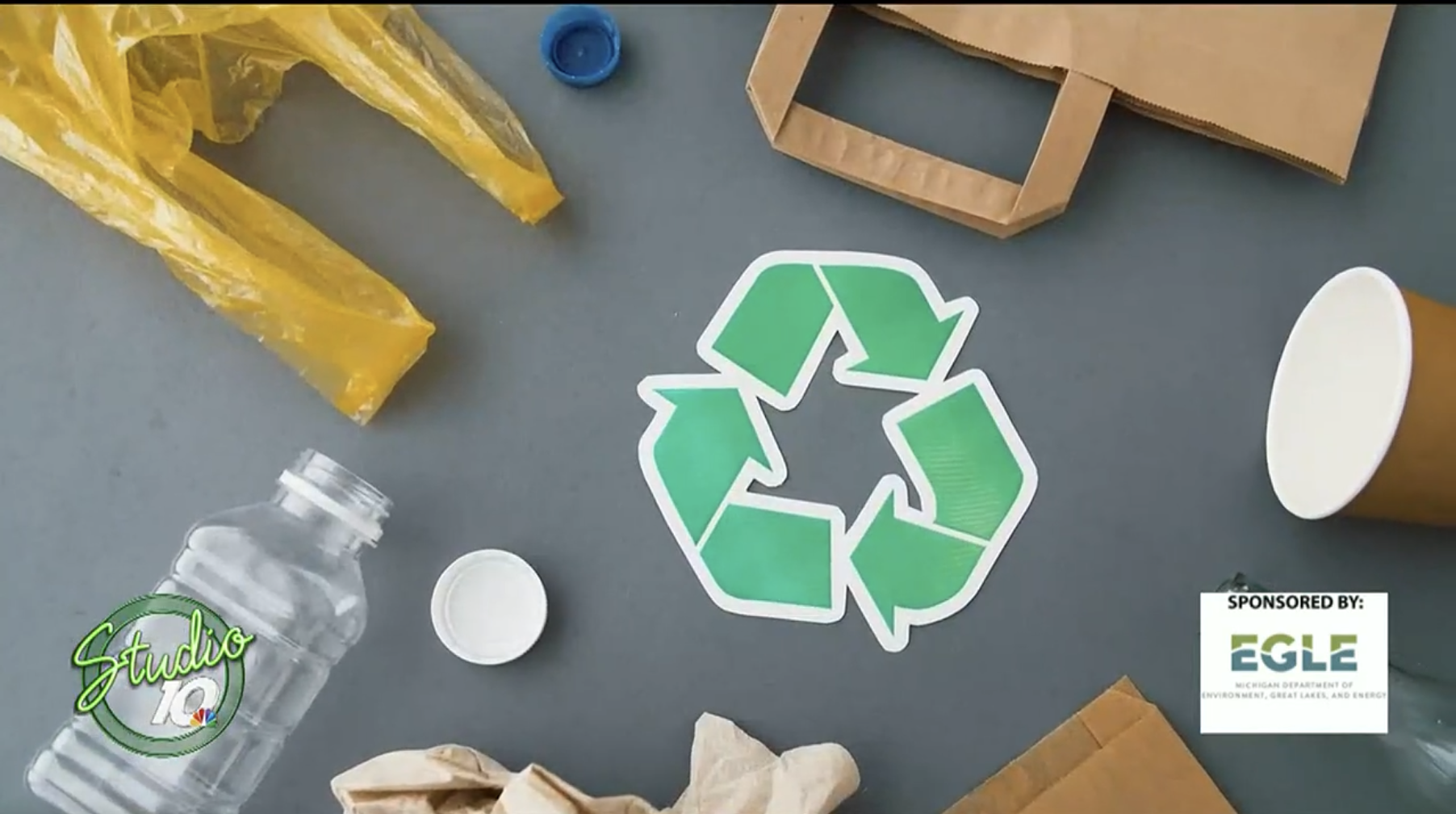 A recycling symbol surrounded by recyclable materials