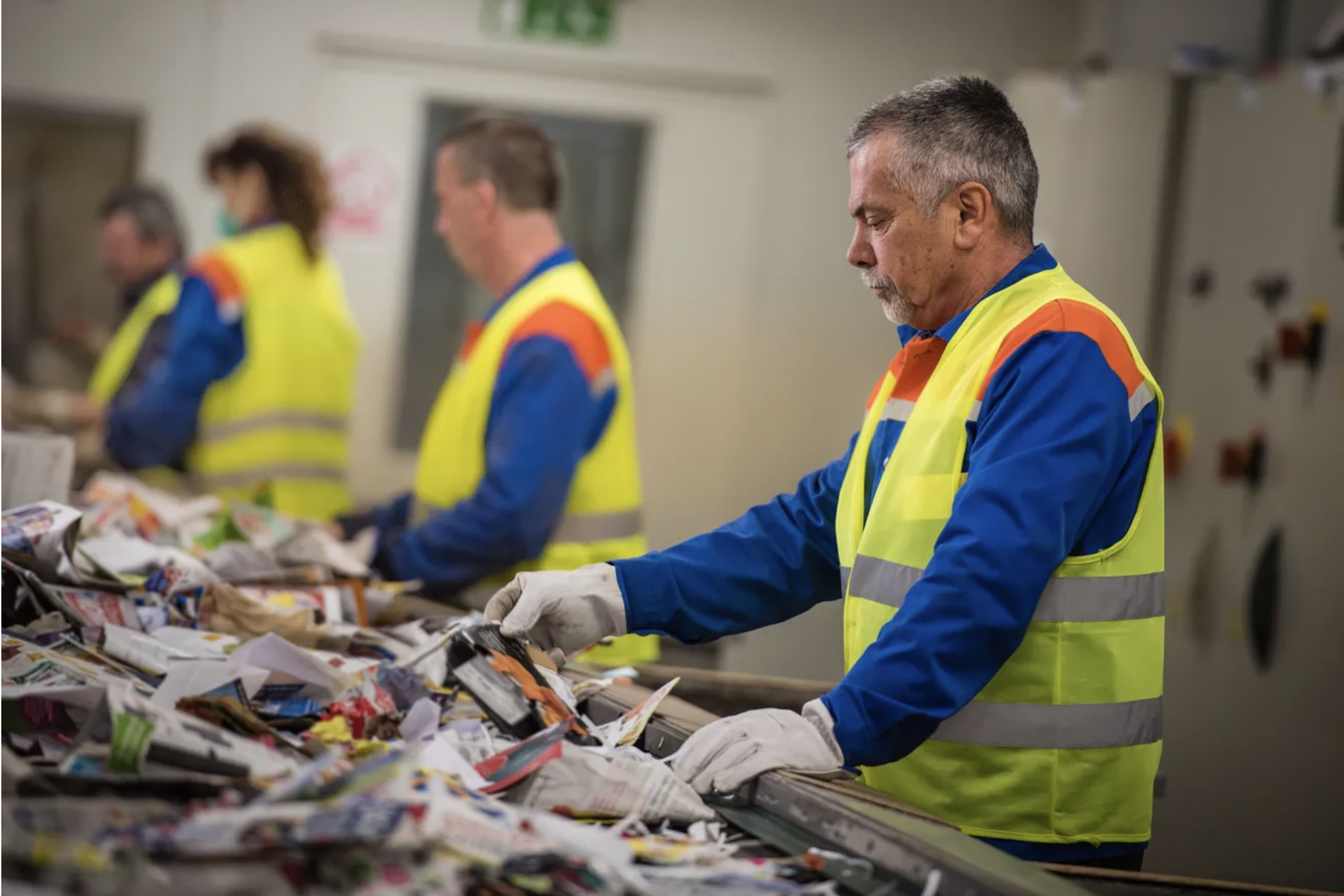 Recycling workers sort materials on the line